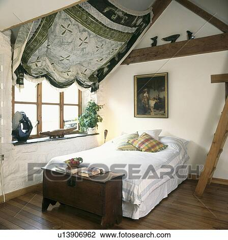 Stock photo of antique chest at the end of the bed in attic country bedroom with fabric draped - Bed plafond ...