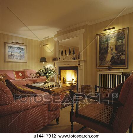 Stock photo of traditional town living room with red sofas for Yellow living room wallpaper