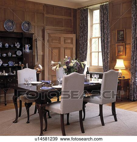 Stock Photograph Of White Upholstered Chairs And Antique Table In Panelled Di