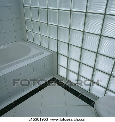 Stock Photo Of Glass Brick Wall And White Floor Tiles With Black Tiled Border Beside Bath In