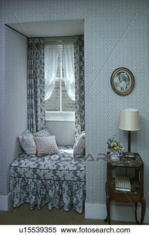 Stock Image of Blue+white patterned windowseat and curtains in ...