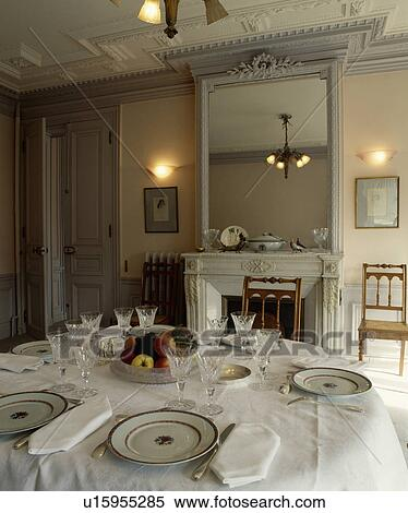 Wall Lights On Either Side Of Ornate Grey Mirror In Traditional Dining Room With Place Settings White Tablecloth