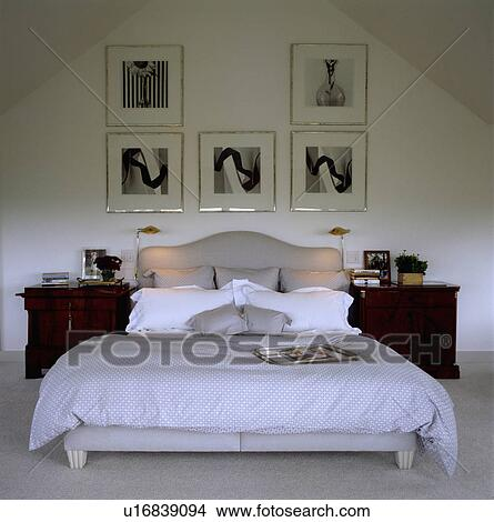 framed blackwhite photographs above grey upholstered bed with white pillows with grey linen in modern bedroom