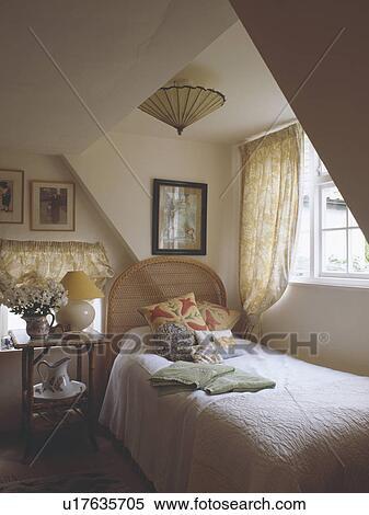 Stock afbeelding bamboe tafel naast enkel bed onder venster in zoldertjes huisje - Traditionele bed tafel ...