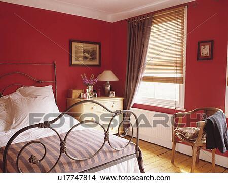 banque de photo orn fer forg lit dans petit rouges chambre coucher beige rideau. Black Bedroom Furniture Sets. Home Design Ideas