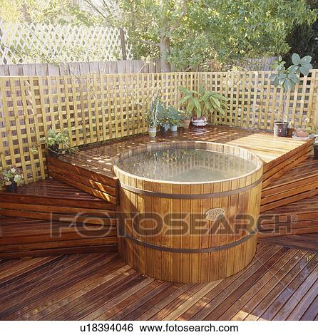 exterior hot tub with decking steps surrounded by trellis fence