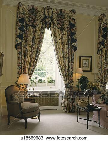 Ornate Pelmet And Patterned Curtains In Livingroom With Lighted Lamps And  Cream Carpet