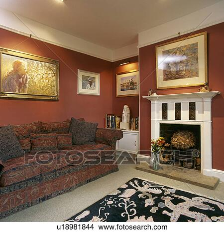 Stock Photo Of Large Patterned Sofa In Terracotta Living Room With White Fireplace And Pictures