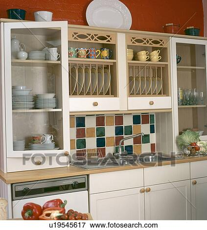 Multi Coloured Tiles Above Stainless Steel Sink In Kitchen With Plate Rack  And Cream Units