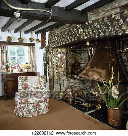 Armchair Beside Inglenook Fireplace In Traditional Cottage Living Room