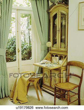 Antique Bureau Beside French Doors With Pastel Green Curtains