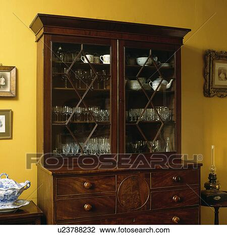 Antique Mahogany Dresser With Glass Doors And China Inside In Yellow Dining Room