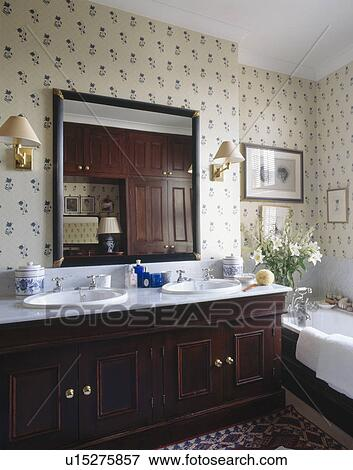 Large mirror above double white basins in mahogany vanity unit in  traditional bathroom with flower patterned wallpaper. Picture of Large mirror above double white basins in mahogany