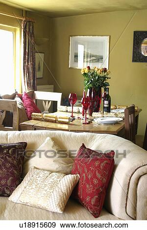 Red And Cream Cushions On Cream Sofa In Front Of Table Set For Lunch In  Green Living And Dining Room