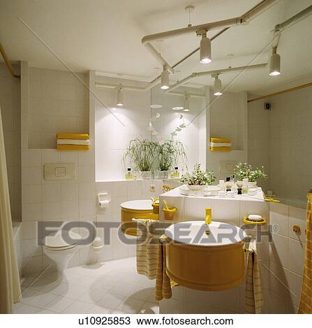 Stock photo of track lighting above yellow basins on white tiled track lighting above yellow basins on white tiled vanity unit in modern white bathroom mozeypictures Choice Image