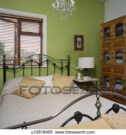 banque de photo traditionnel noir m tal lit devant fen tre slatted bois aveugle. Black Bedroom Furniture Sets. Home Design Ideas