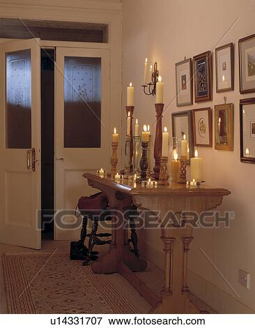 lighted candles in tall on wooden console table in hall with engraved glass panels in double doors - Tall Console Table