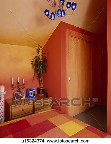 Stock photo of fitted wardrobe in orange bedroom with - Orange and light blue bedroom ...