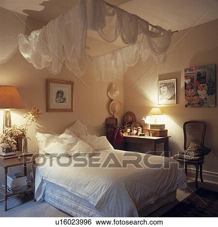banque d 39 images romantique chambre coucher blanc voile baldaquin et doux clairage. Black Bedroom Furniture Sets. Home Design Ideas