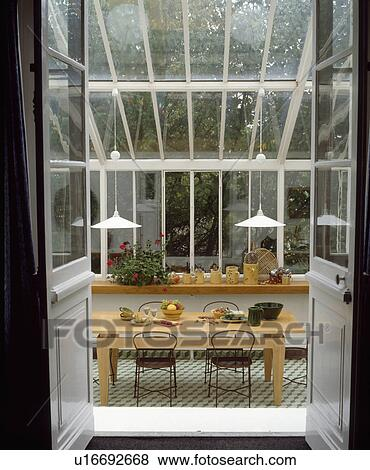 Open Double Doors To Modern Wood Table And Black Chairs In Glass Conservatory Dining Room