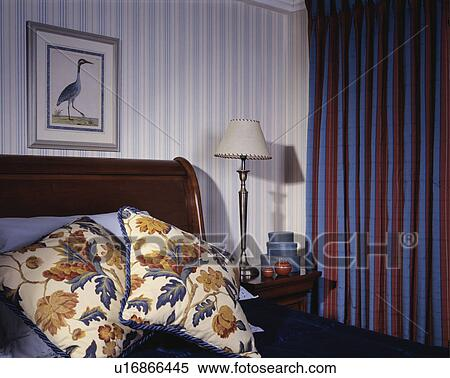 floral cushions on bed in hotel bedroom with redblue striped curtains and bluewhite striped wallpaper