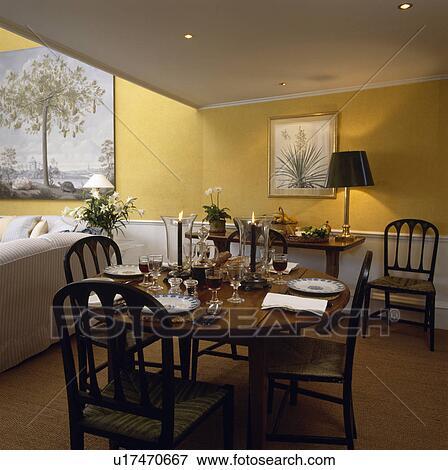 Beeld antieke circulaire tafel en stoelen in gele tachtig eetkamer met sisal tapijt - Tapijt eetkamer ...