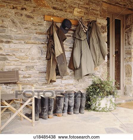 Beelden jassen op steenmuur boven wellington laarzen op veranda u18485438 zoek stock - Beelden van verandas ...