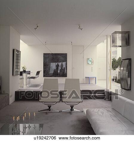 Stock afbeeldingen witte bank en chroom en leerstoelen in openplan modern leven kamer - Moderne witte kamer ...