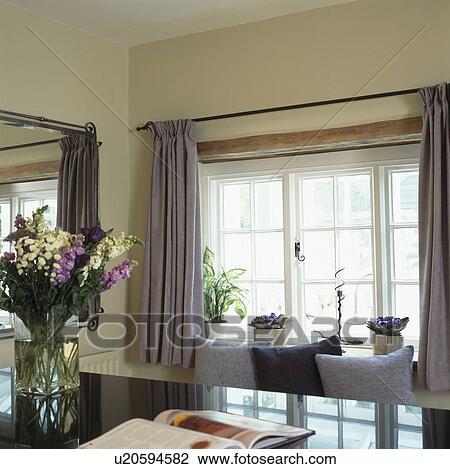 Stock foto grijze gordijnen boven sofa in hippe for Grijze gordijnen