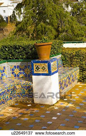 image terre cuite pot sur plinth dans jardin espagnol bleu et jaune mur carrel. Black Bedroom Furniture Sets. Home Design Ideas