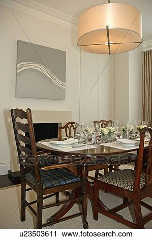 Modern Circular Light Fitting Above Place Settings On Antique Table With  Matching Chairs In Modern Dining Room Part 90
