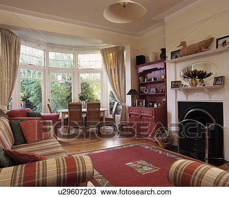 Dining Table And Chairs In Bay Window Of Living Room With Patterned Red Rug Front White Fireplace