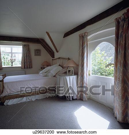 Stock fotografie zonnig land slaapkamer met grijze tapijt en circulaire tafel met - Traditionele bed tafel ...