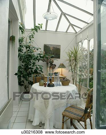 Pictures of Wicker chair and circular table with white cloth in ...