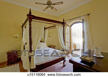 White Drapes And Linen On Fourposter Bed In Pale Yellow Spanish Country Bedroom With French Doors Open To Patio