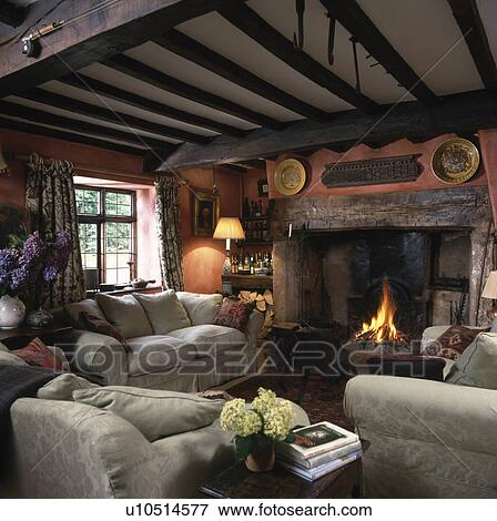 Patterned Beige Sofas In Cottage Living Room With Beamed Ceiling And Lighted Fire Inglenook Fireplace