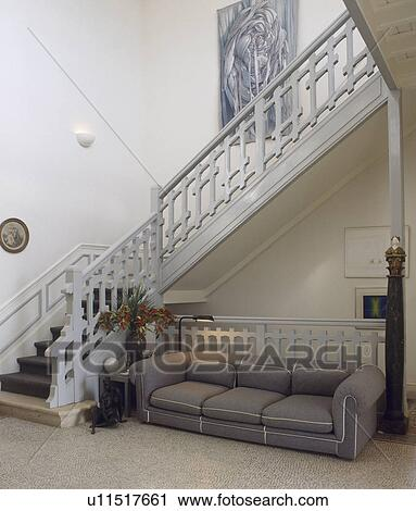 Large Grey Sofa And Pale Grey Wooden Staircase In Hall With Terrazo Floor