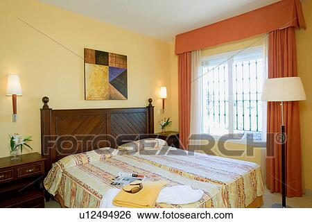 Orange Curtains At Window In Pale Yellow Bedroom With Yellow Patterned  Linen On Mahogany Bed