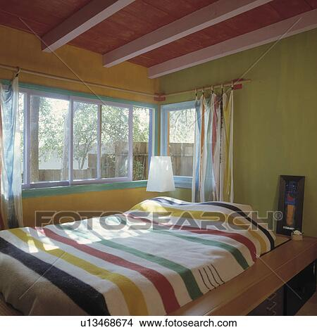 Stock photo of multicoloured striped blanket on bed in yellow and green bedroom with pink and - Bed plafond ...