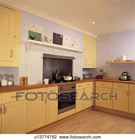 Stock photo of wooden flooring and stainless steel oven in for Mauve kitchen walls