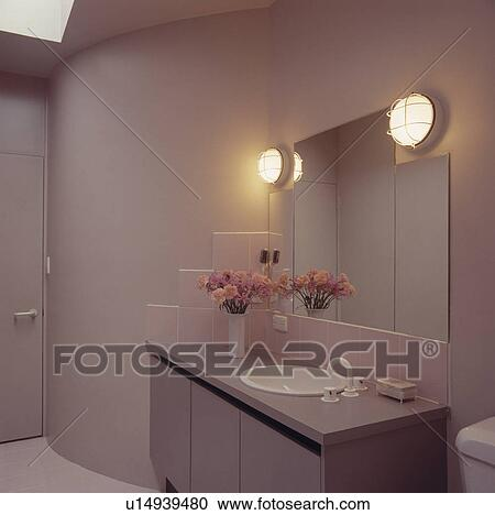 Stock Photography of Bulkhead lights on either side of mirror above fitted vanity unit with ...