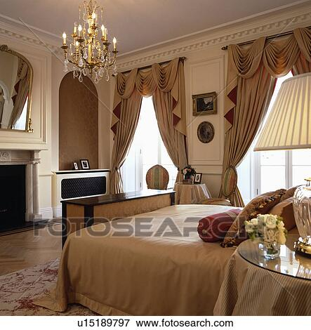 Lighted Antique Glass Chandelier Above Bed Bed In Opulent Bedroom With  Swagged And Tailed Curtains