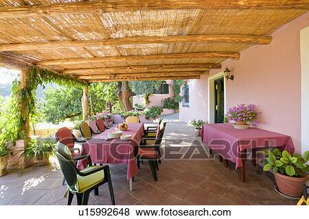 Beelden bamboe zonwering op stoelen met kleurrijke kussens en tafels met roze - Beelden van verandas ...