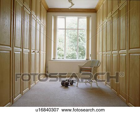 Beeld lloyd weefgetouw stoel en dumbells op grijze tapijt in kleedkamer met bleek - Tapijt badkamer hout ...