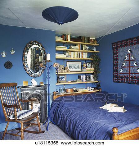 Immagini sedia dondolo accanto caminetto in blu - Mensole dietro letto ...