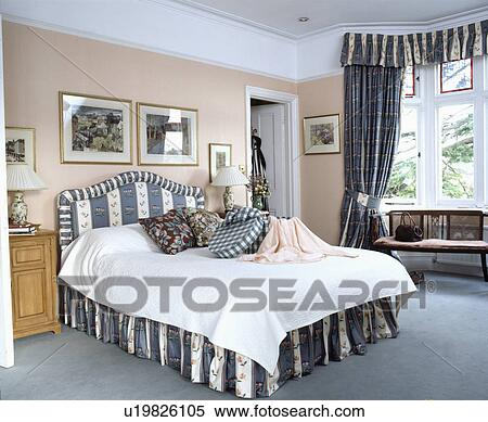 Stock Image of Grey striped and floral upholstered bed and ...
