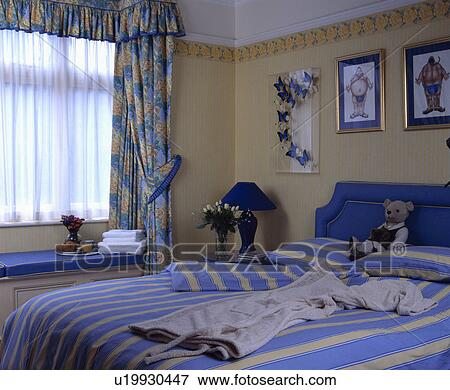 Picture of Blue+yellow striped quilt and pillows on bed in neutral ...