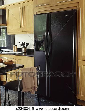 Large Black American Style Fridge Freezer In Modern Fitted Kitchen With  Pale Wooden Fitted Cupbaords
