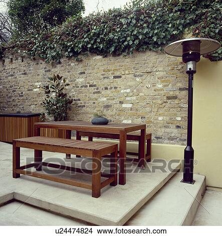 Patio Heater And Hard Wood Table And Benches On Raised Paved Patio In Small  Walled City Garden