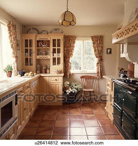 stock foto terracotta fussbodenfliesen und schwarz aga in h tte kueche mit blumen. Black Bedroom Furniture Sets. Home Design Ideas